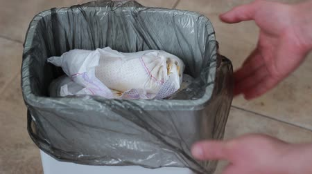 változás : Used diapers in the trash. Mom throws dirty diapers in the bin. Waste Recycling
