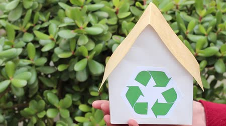 sustain : Energy saving, real estate and family home concept. People, ecology, environment and conservation concept - close up of hands holding house with green recycling sign