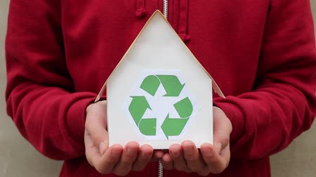 sustain : Hands of young man holding a paper house with recycling symbol. People, ecology, environment and conservation concept - close up of hands holding house with green recycling sign Stock Footage