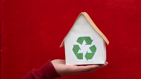 sustain : People, ecology, environment and conservation concept - close up of hands holding house with green recycling sign