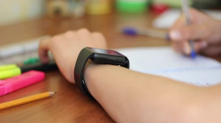 e book : Young Student E-Learning Using Smart Watch. Smart Watches in Education. May depict third party IP Stock Footage
