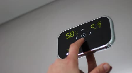 przycisk : Smart thermostat. Touch Panel. Digital programmable thermostat. The user adjusts the temperature. Controlling a homes heating. Energy saving