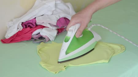 гладильный : Washing and ironing baby clothes. Woman ironing newborn cloth Стоковые видеозаписи
