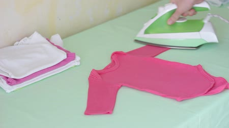 žehlení : Mother ironing infant bodysuits. Washing, Ironing and folding newborn clothes