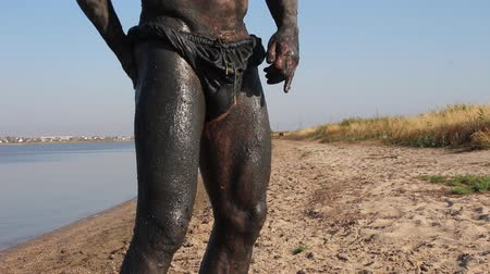 mud bath : Mud cure. Bather covered with mud at the lake. Mud-baths (balneotherapy), and the dirt and water used to mix mud baths may also contain minerals Stock Footage