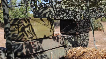 patron : Wooden boxes with weapons and ammunition in a military camp. Camouflage netting is draped away from a military box to reduce its shadow