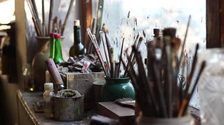palette knife : The windowsill. Old paintbrushes in a creative workshop. Artist Equipment Stock Footage