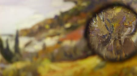 restorer : Art expert at work using a magnifying glass on fine detail art. Colorful paint smears on canvas close up