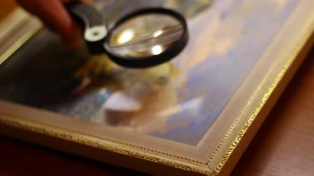 restorer : Art expert at work using a magnifying glass. Painting