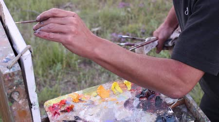 palette knife : Artist Working En Plein Air. Oil on canvas. Landscape Painting. The left handed man
