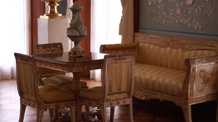 opona : The Blue Drawing Room with intricate plasterwork decorating the walls. The white furniture with gilt ornaments overlaid. A house interior with luxurious and classical retro style