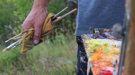 felpudo : Hands soiled with oil paint. Portable easel with built-in paint box and palette. Painting outdoors, capturing natural light in the landscape, and translating those qualities with paint to canvas Vídeos