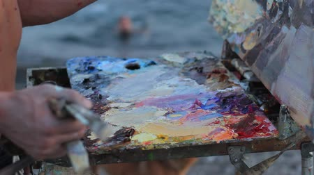 şövale : Oil painting on the sea. Hands of the artist. Oil painting Using palette knives, oil painting brushes and rags. Summer evening