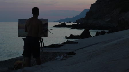 şövale : Silhouette of the artist who paints beautiful sunset on the rocky coast