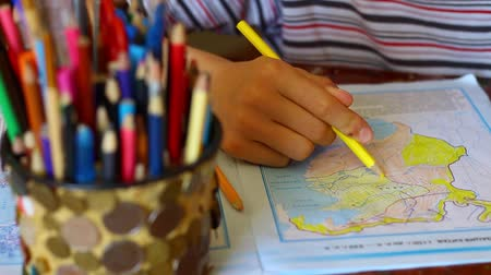 ansiklopedi : Book Of Outline Maps. Drawing With Pencil. Schoolchild adds symbols, labels, and other information to the maps for hands-on learning