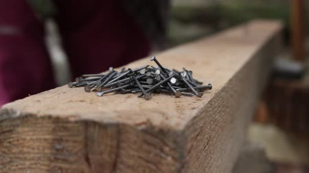 fél : Hammering a nail into the wood. A bunch of nails, Close up
