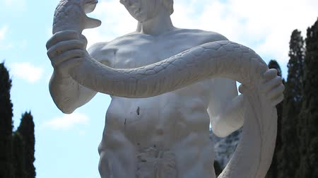 arte : Heracles strangling a snake. Stone sculpture in the alley