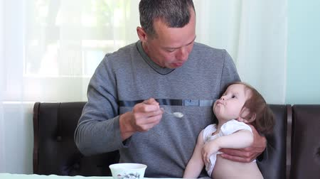 puericultura : Father feeds baby with spoons. Adult male on maternity leave. Modern family Stock Footage