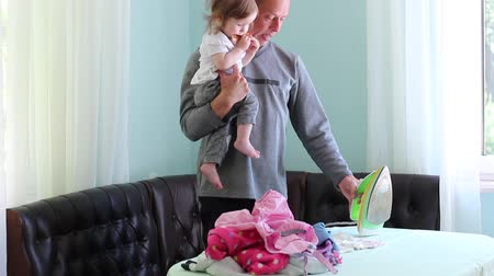 žehlení : Father and baby. Ironing childrens clothes. A man in non-traditional gender role. Childcare and housework