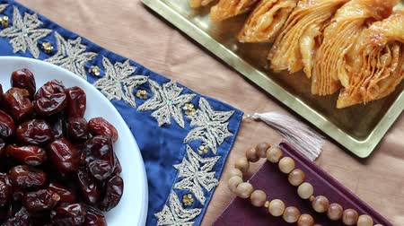 holy book : Islamic Celebration Foods and Quran. Celebrating Eid al-Fitr, the End of Ramadan, With Sweet, Traditional Treats Stock Footage