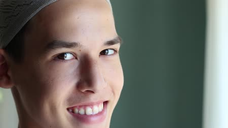 mianmar : Young arabian man smiles. Eid al-Fitr. Young muslim man with prayer cap smiling Stock Footage