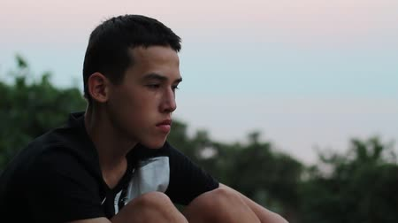 wistful : Sorrowful Young Boy In The Evening. Teen Sits Alone Looking Sad Or Worried. Summer sky, sunset