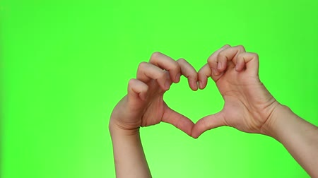 nonverbal : A hand heart. Person forms a heart shape using their fingers. Two handed gestures. Chromakey. Green Screen. Isolated