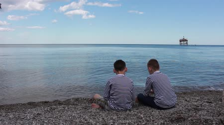 expedição : Two Boys Sit On The Beach And Look At The Sea