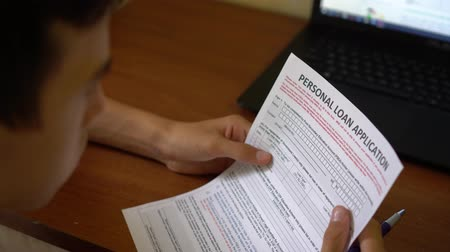 žádost : A young man is applying for a personal loan. Credit application form on a paper sheet