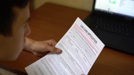 aprovado : A young man is applying for a car loan. Credit application form on a paper sheet
