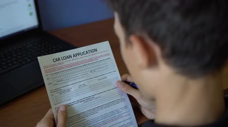 financiamento : A young man is applying for a car loan. Credit application form on a paper sheet
