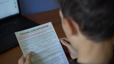 financiamento : A young man is applying for a personal loan. Credit application form on a paper sheet
