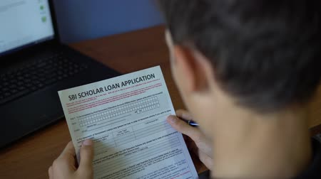 financiamento : A young man is applying for a student loan. Credit application form on a paper sheet