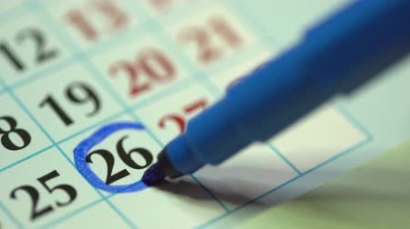 mensal : 26th – twenty-sixth day of the month. The woman marks the calendar date with a blue marker. Business Wall Calendar Planner and Organizer