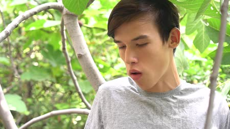Young handsome man eating fresh ripe fig fruit