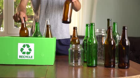 A man disposes of recyclable glass separated by colour: brown, green and white Stock Footage