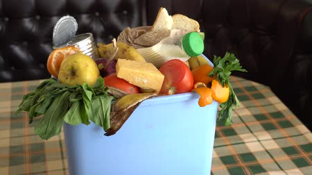 Food Loss and Waste Reduction. Leftovers from a meal, expired food, stale food, and blemished fruits and vegetables in the trash bin. Concept of zero waste and caring for environment Stock Footage
