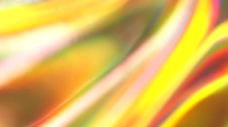 Holographic foil yellow orange red iridescent abstract motion background. Luminous surreal blurred moving gradient