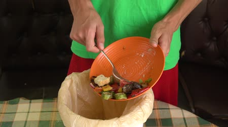 A man throws leftovers of a vegetable vegetarian meal from a plate into a compost bucket. Food waste reduction. Sorting of household waste, composting, recycling, zero waste Стоковые видеозаписи