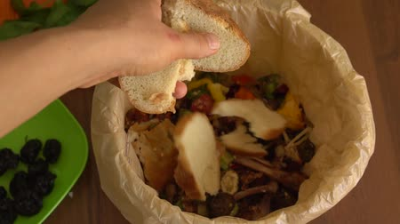 A woman throws the remains of uneaten bread into the bin. Food waste reduce. Sorting of household waste, composting, recycling, zero waste Стоковые видеозаписи