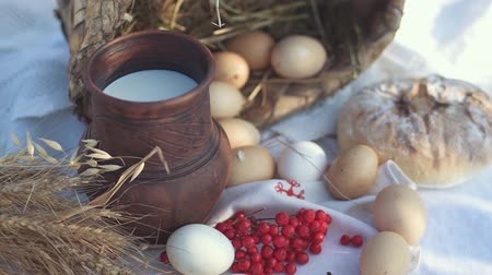 üvez ağacı : A jug of milk and chicken eggs in a wicker basket on a table with a tablecloth