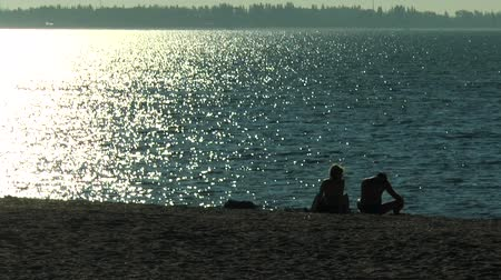 mehtap : Man and woman sitting near the sea with moonlight