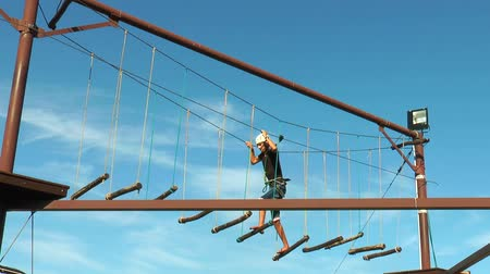 corda : The young man goes on a rope road on a background of blue sky Rope park