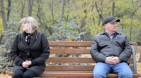 separação : Man and woman looking in different directions while sitting on the bench