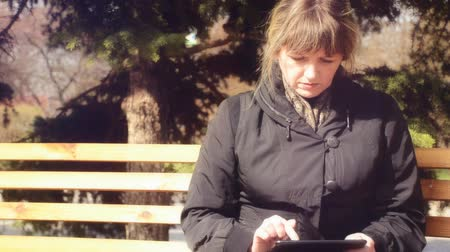 açık kahverengi : Woman working with the tablet. In the background you can see a bird on a branch of spruce Stok Video