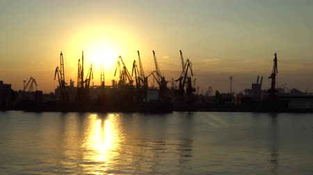 tersane : Sunset at the seaport. One can see the reflection of the sun and the outlines of cranes