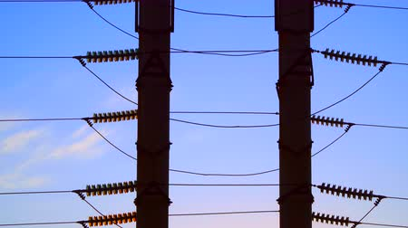 distribution lectrique : Insulators on poles high-voltage line on the sky background. Insulators are illuminated by the setting sun Stock Footage