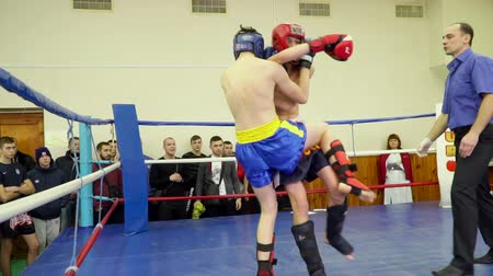 teen action : Mariupol, Ukraine - November 26, 2016: The city championship in kickboxing .Two athletes in the ring blows from each other.