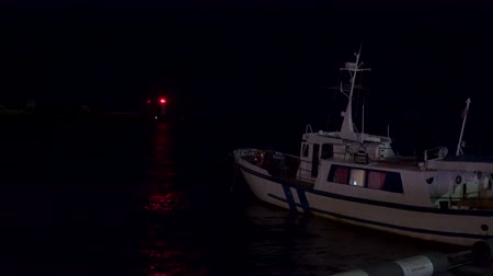 Fishing boat on the pier at night. On the horizon there is a beacon