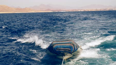 hawser : The motor boat is tied with a rope to a floating yacht. The Red Sea Egypt